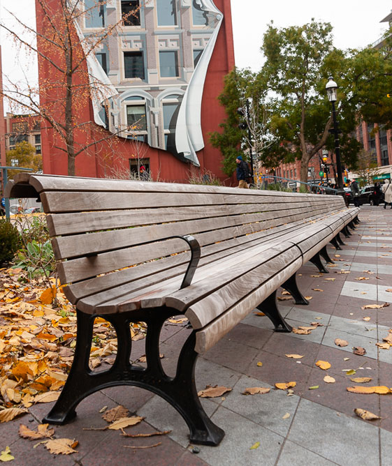 A long wooden park bench in Downtown Toronto