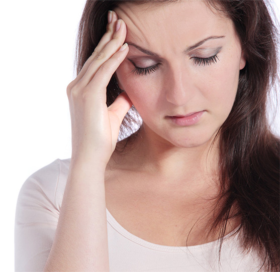 Young woman rubs forehead after sedation