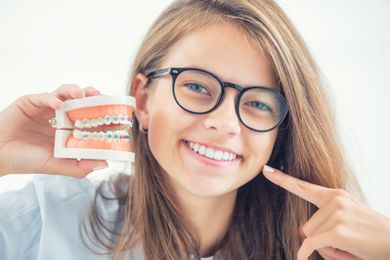 Girl with glasses showing off straight teeth after dental braces