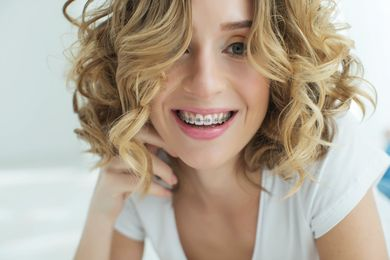 Curly-haired woman smiling with braces