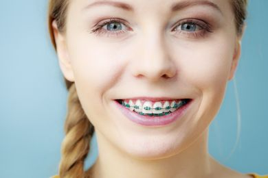 Smiling young woman showing teeth with braces