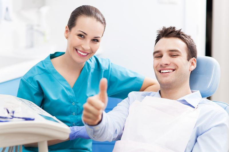 Man giving thumbs up after teeth cleaning in Toronto dental office