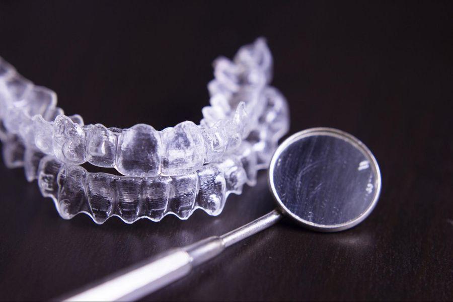 Invisalign aligner and dental mirror on desk in Toronto dental office